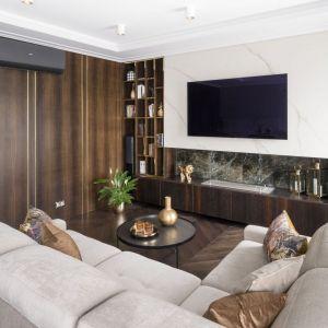 Ściany w salonie wykończone są ciemnym fornirem w kolorze czarnego wędzonego dębu, białą farbą oraz pięknym, naturalnym kamieniem. Projekt: Magdalena Miśkiewicz, Miśkiewicz Design. Fot. Łukasz Zandecki