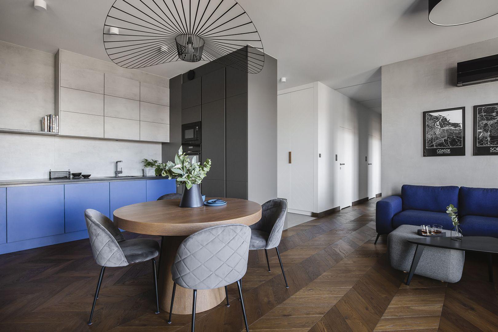 Szara kuchnia z drewnianą podłogą i kolorem niebieskim, który pięknie ożywia wnętrze. Projekt: make Architekci. Fot. Hanna Połczyńska, Kroniki Studio