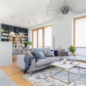 Piękny jasny salon z szarą kanapą na środku. Projekt: Renee's Interior Design Fot. Marta Behling Pion Poziom - Fotografia Wnętrz