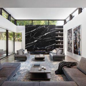 W czarno-białym salonie prawdziwą gwiazdą jest ściana z kominkiem, z pięknym rysunkiem kamienia. Projekt: Cecconi Simone. Fot. Studio Shai Gil