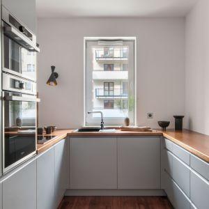 Mała kuchnia w bloku urządzona w szarościach i ocieplona drewnem. Projekt: Deer Design. Fot. Dariusz Majgier