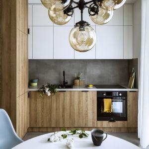 Mała kuchnia w bloku, która pięknie łączy biel i drewno. Projekt: Poco Design. Fot. Yassen Hristov