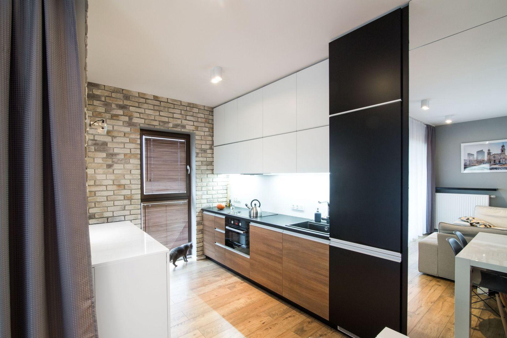 Mała kuchnia w bloku, w której biel pięknie łączy się drewnem oraz czernią. Projekt i zdjęcia: Joanna Nawrocka