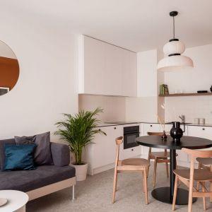 Mała kuchnia w bloku połączona z jadalnią oraz z salonem. Urządzona w bieli. Projekt: pracownia 3XEL. Fot. Dariusz Jarząbek