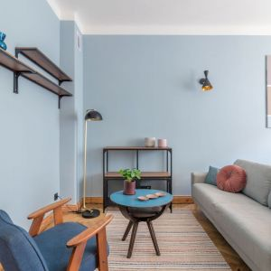 Mały, prosty stolik niebieskim blatem w małym salonie. Projekt i stylizacja wnętrza: Ola Dąbrówka, pracownia Good Vibes Interiors. Fot. Marcin Mularczyk