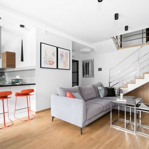 Biały salon z drewnem połączony z kuchnią i jadalnią. Projekt: MM Architekci. Fot. Jeremiasz Nowak