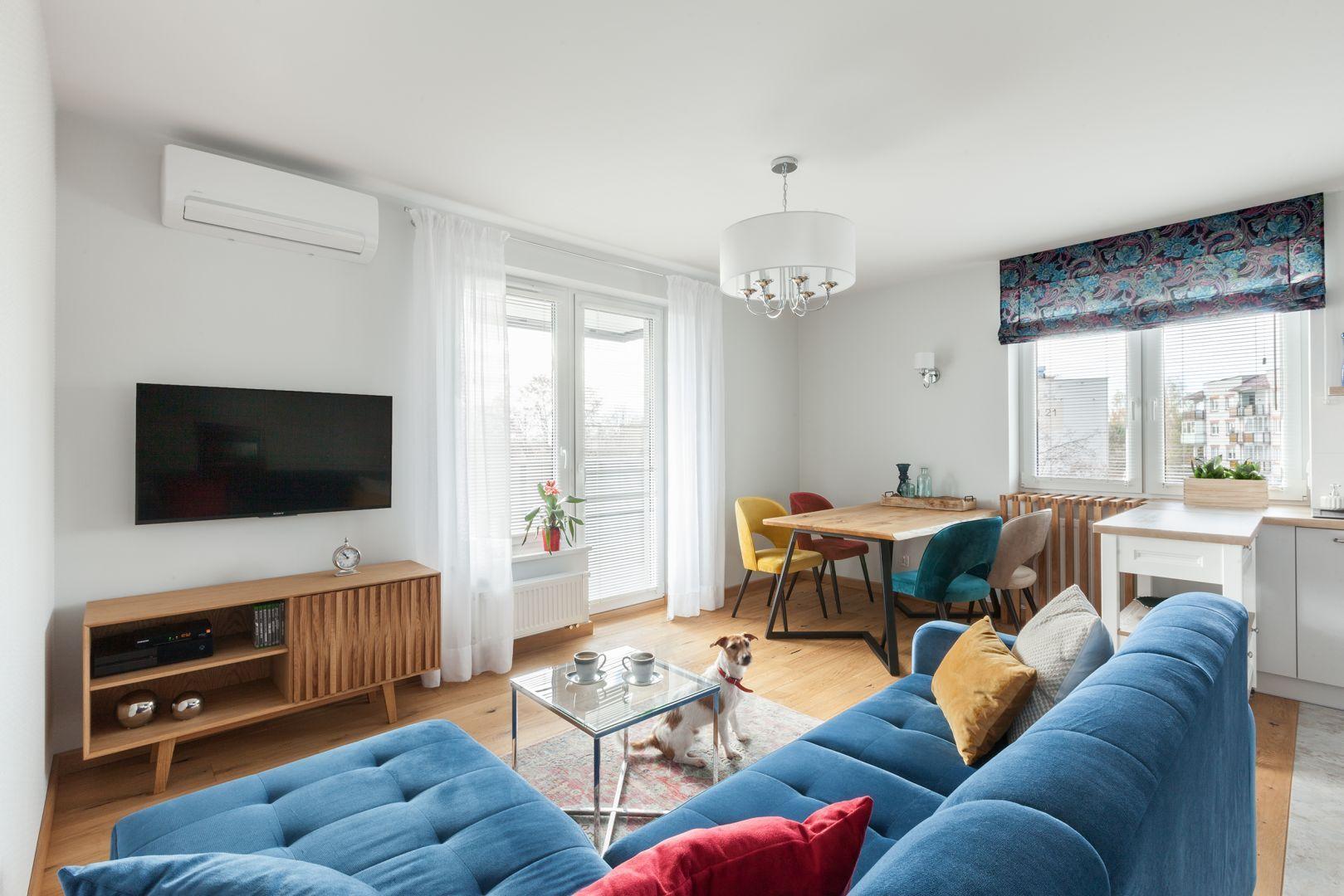 Biały salon z drewnem pięknie ożywiają kolorowe dodatki. Projekt: Justyna Mojżyk, poliFORMA. Fot. Monika Filipiuk-Obałek
