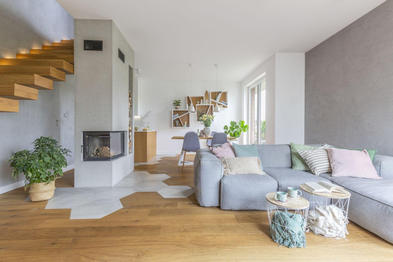 Drewniana podłoga w ciepłym kolorze i chłodny beton na ścianie. Projekt: Zu Projektuje. Fot. Pion Poziom