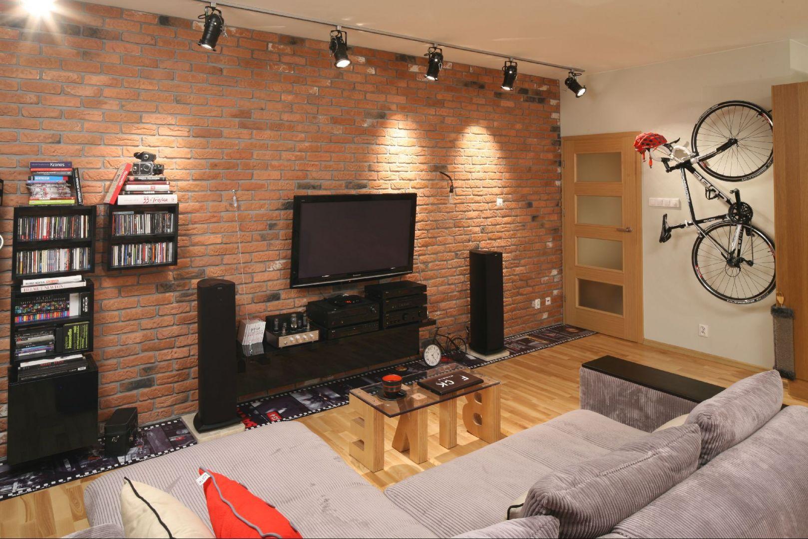 Cegła na ścianie to modny, ale przytulny element tego salonu. Podłoga to wyraźny i ciepły wzór drewna. Proj. wnętrza Iza Szewc, Fabryka Nastroju