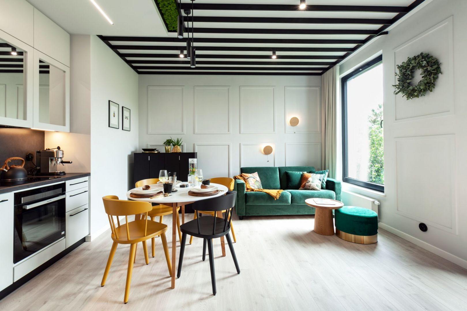 Sofa w kolorze głębokiej zielenie. Projekt Arkadiusz Grzędzicki Projektowanie Wnętrz. Fot. Olga Kharina, XO foto.
