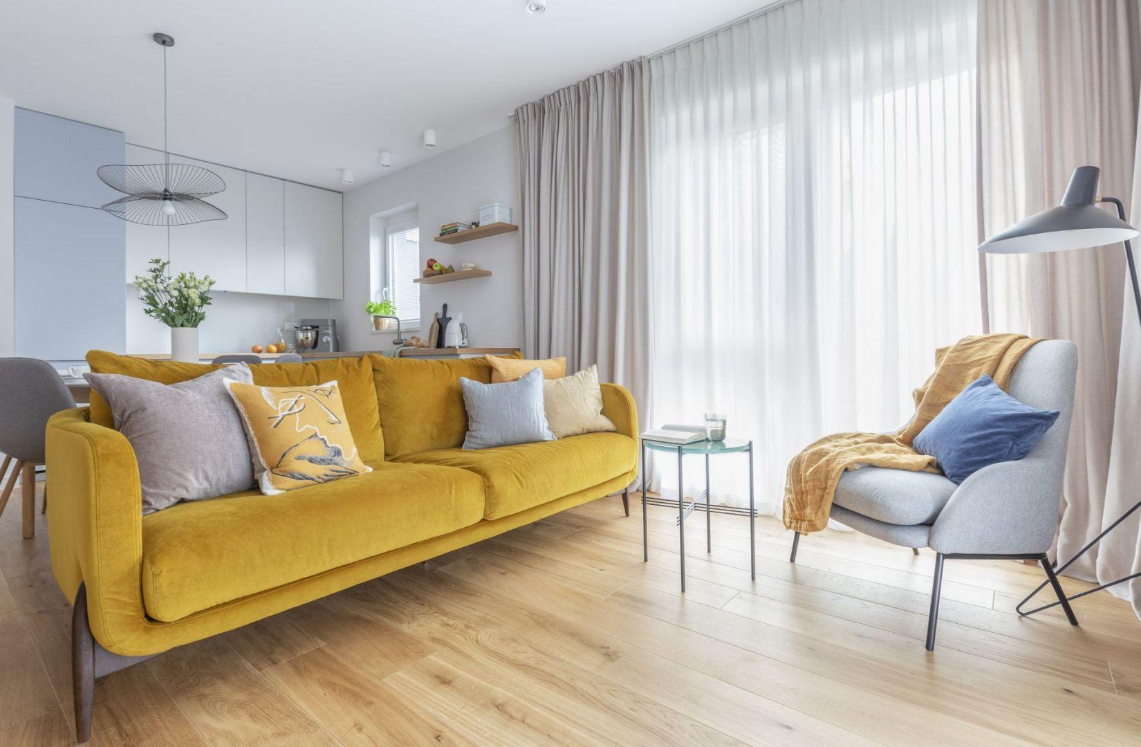 Szary fotel w zastawie z żółtą sofa w małym salonie. Projekt: Decoroom Pracownia Architektury. Fot. Marta Behling, Pion Poziom – fotografia wnętrz