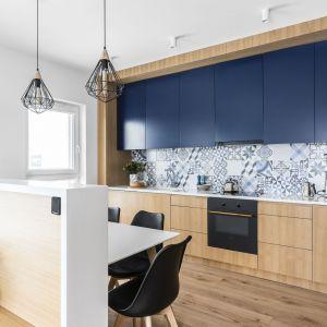 Niebieskie płytki inspirowane stylem śródziemnomorskim na ścianie nad blatem przytulnej kuchni. Projekt: pracownia Magma. Fot. Fotomohito