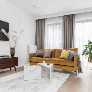 Jasny salon ożywiony piękną kanapą w kolorze musztardowym. Projekt: Katarzyna Szostakowska, Kate&Co. Fot. Marta Behling z Pion/Poziom