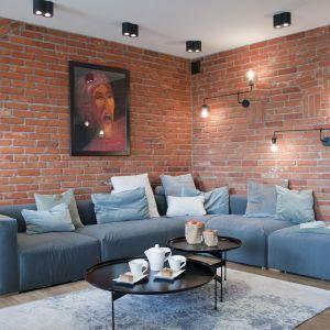 Cegła na ścianach to bardzo mocny akcent w salonie. kanapa w chłodnym kolorze łagodzi nieco jej intensywność. Projekt: Ewelina Mikulska-Ignaczak, Mikulska Studio. Fot. Jakub Ignaczak, K1M1