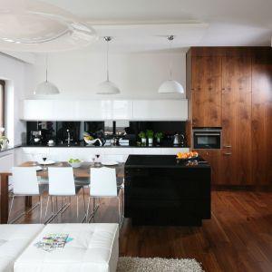 Duża wyspa połączona z praktycznym stołem oddziela kuchnię od salonu. Projekt: Agnieszka Ludwinowska. Fot. Bartosz Jarosz