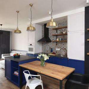 Wyspa w kuchni połączona ze stołem, który pełni rolę jadalni. Projekt: Anna Krzak. Fot. Bartosz Jarosz