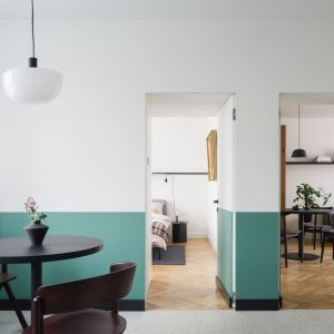 Z kuchni można przejść do sypialni oraz do salon, którego wnętrze nie przytłacza dużą ilością mebli. Projekt: pracowni 3XEL. Fot. Dariusz Jarząbek