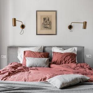 Ściana za łóżkiem w sypialni wykończona jest farbą w jasnym szarym kolorze. Sypialnie jest jasna i przytulna. Projekt: pracownia and.home. Fot. Katarzyna Seliga-Wróblewska, Marcin Wróblewski/Fotomohito