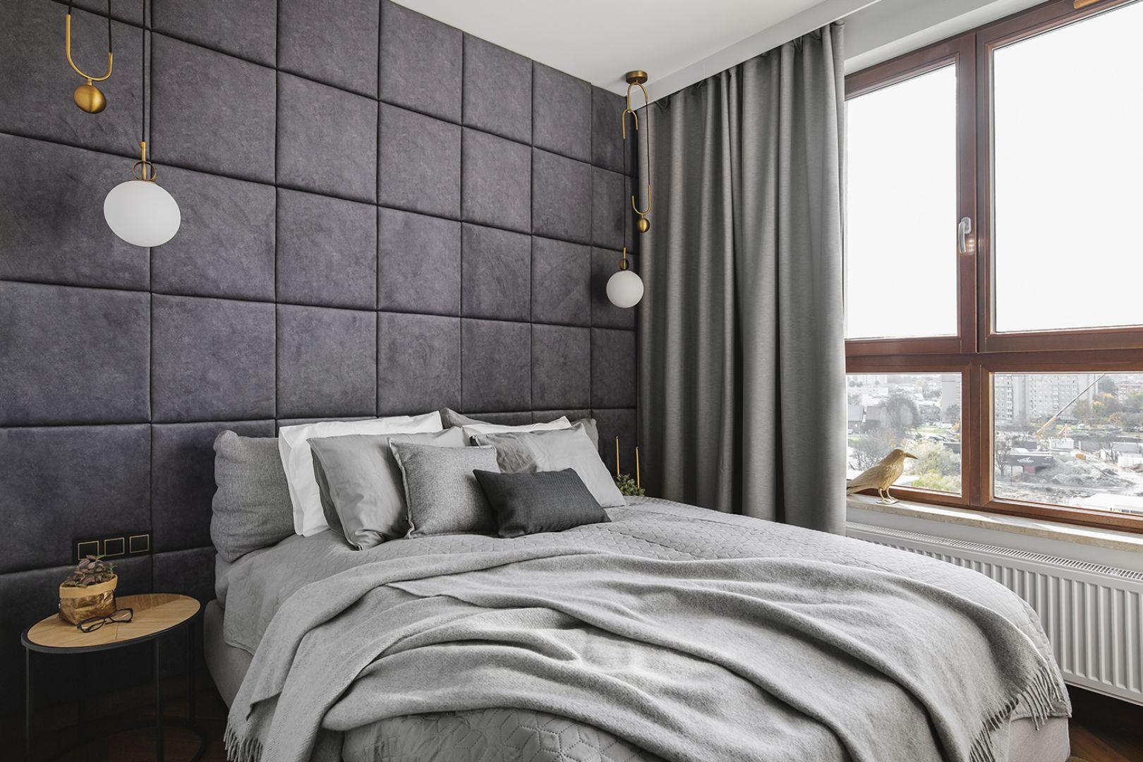 Ściana za łóżkiem wykończona jest tapicerowanymi panelami w szarym kolorze. Projekt: make Architekci. Fot. Hanna Połczyńska, Kroniki Studio