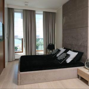 Ściana za łóżkiem w sypialni wykończona jest tapicerowanym zagłówkiem w brązowym kolorze. Projekt: Anna Maria Sokołowska. Fot. Bartosz Jarosz