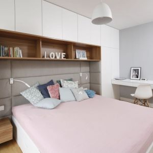 Ściana za łóżkiem wykończona jest miękkimi panelami, nad którymi dodatkowo znajdują się półki. Projekt: Przemek Kuśmierek. Fot. Bartosz Jarosz