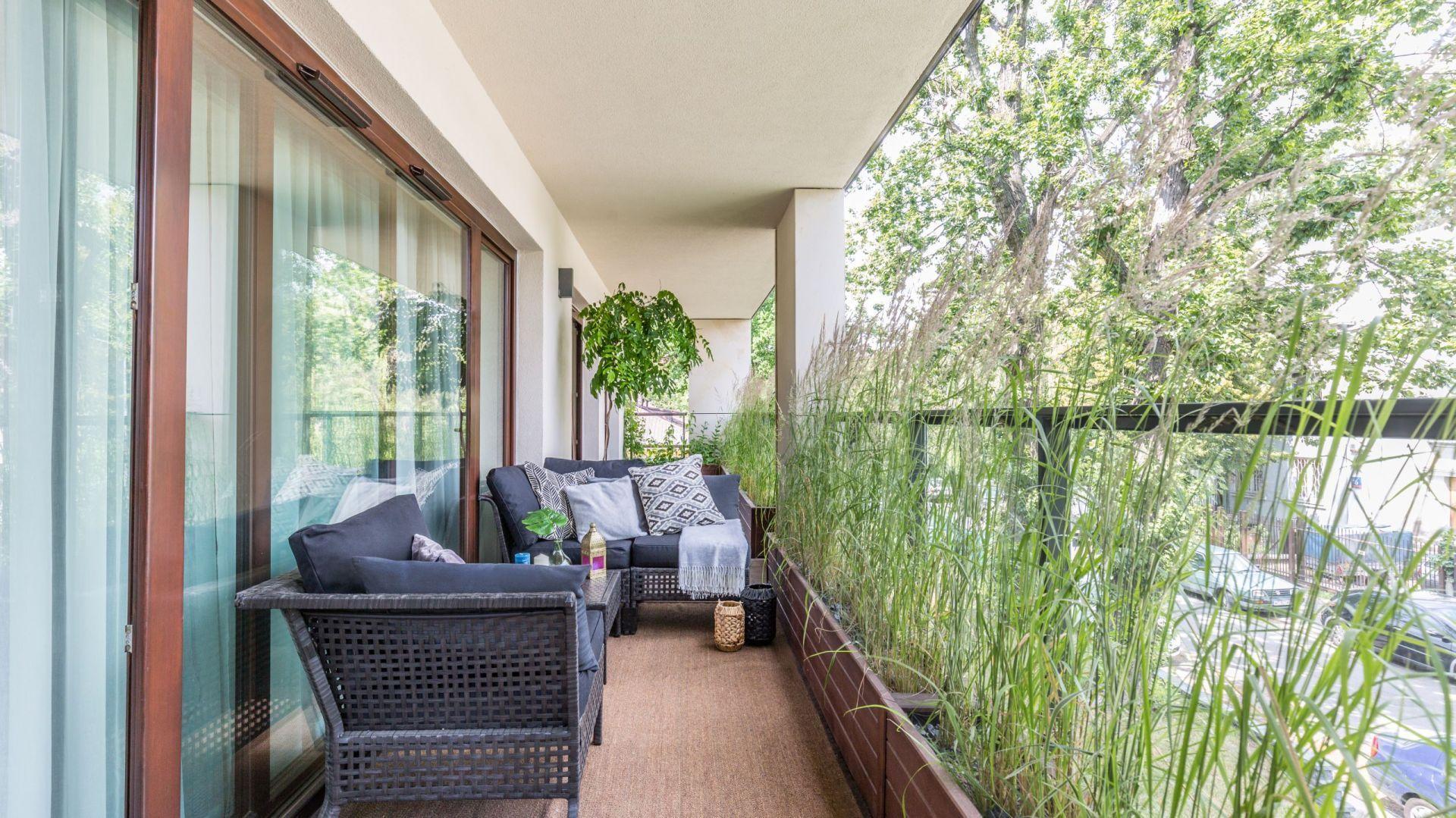 Na balkonie zmieściła się wygodna, dwuosobowa sofa, fotel oraz stolik. Rośliny stanowią subtelną osłonę przed wzorkiem sąsiadów. Projekt: Malwina Koziestańska. Fot. Pion Poziom