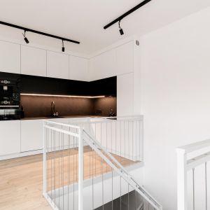 W kuchni architektka postawiła na biały i czarny matowy lakier na frontach kuchennych oraz czarny blat z efektem kamienia z konglomeratu. Realizacja i zdjęcia: MÁS Estudio