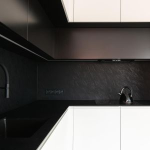 Czarny blat z efektem kamienia z konglomeratu idealnie pasuje do czarne ściany nad blatem. Realizacja i zdjęcia: MÁS Estudio