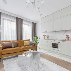Kuchnia z salonem w bloku urządzona w jasnych kolorach. Białe meble w kuchni idealnie pasuję do kolorowej sofy. Projekt: Katarzyna Szostakowska, Kate&Co. Fot. Marta Behling z PionPoziom