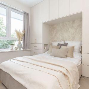 Mała sypialnia w bloku, w której króluje tu biel oraz piaskowy beż. Projekt: Decoroom Fot. Marta Behling Pion Poziom
