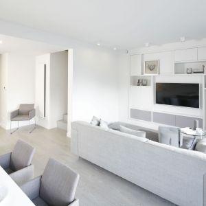 Szafka pod telewizor w salonie w szarym kolorze. Idealnie pasuje do białej aranżacji. Projekt: Przemek Kuśmierek. Fot. Bartosz Jarosz