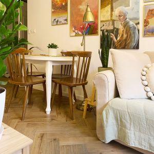Klasyczny biały, okrągły stół z drewnianymi krzesłami, pamiętającymi lata 50 XX w., pięknie prezentuje się w niedużym wnętrzu. Projekt i zdjęcia: Duch ProjektanciProjekt i zdjęcia: Duch Projektanci