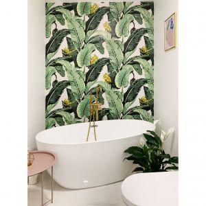 W łazience znajduje się piękna, wolnostojąca wanna ze złotą baterią oraz wzorzysta tapeta(banana jungle), która nadaje wnętrzu charakteru. Projekt i zdjęcia: Duch Projektanci
