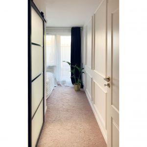 Ściana ciągnąca się od wejścia do pokoju aż po drzwi na ogródek, została za pokryta sztukaterią. Projekt i zdjęcia: Duch Projektanci