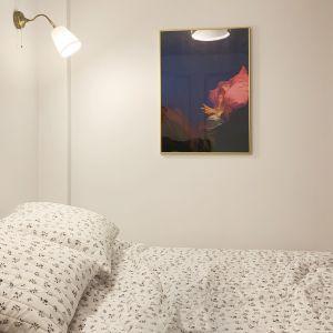 Aranżację jasne sypialni dopełniają dwa złote, klasyczne kinkiety nad łóżkiem oraz obraz znajdujący się na prostopadłej ścianie. Projekt i zdjęcia: Duch Projektanci