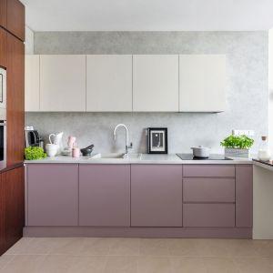 Meble kuchenne to połączenie białych frontów na szafkach wiszących oraz różowych, matowych frontów na szafkach dolnych. Projekt: Decoroom. Fot. Pion Poziom