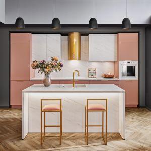 W nowoczesnej kuchni z wyspą kolor różowy doskonale połączono ze złotem oraz z dekorami wytwornego marmuru. Kuchnia KAM Premium. Plus. Fot. KAM