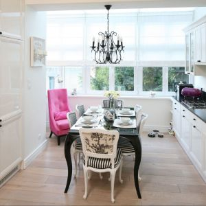 Różowy fotel stanowi świetny dodatek do białej, klasycznej kuchni z jadalnią. Projekt: Małgorzata Galewska. Fot. Bartosz Jarosz