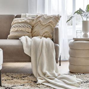 Beżowe dodatki i dekoracje, takie jak poduszki, stolik kawowy, pled dobrze sprawdzą się w salonie w stylu plażowym lub boho. Fot. WestwingNow.pl