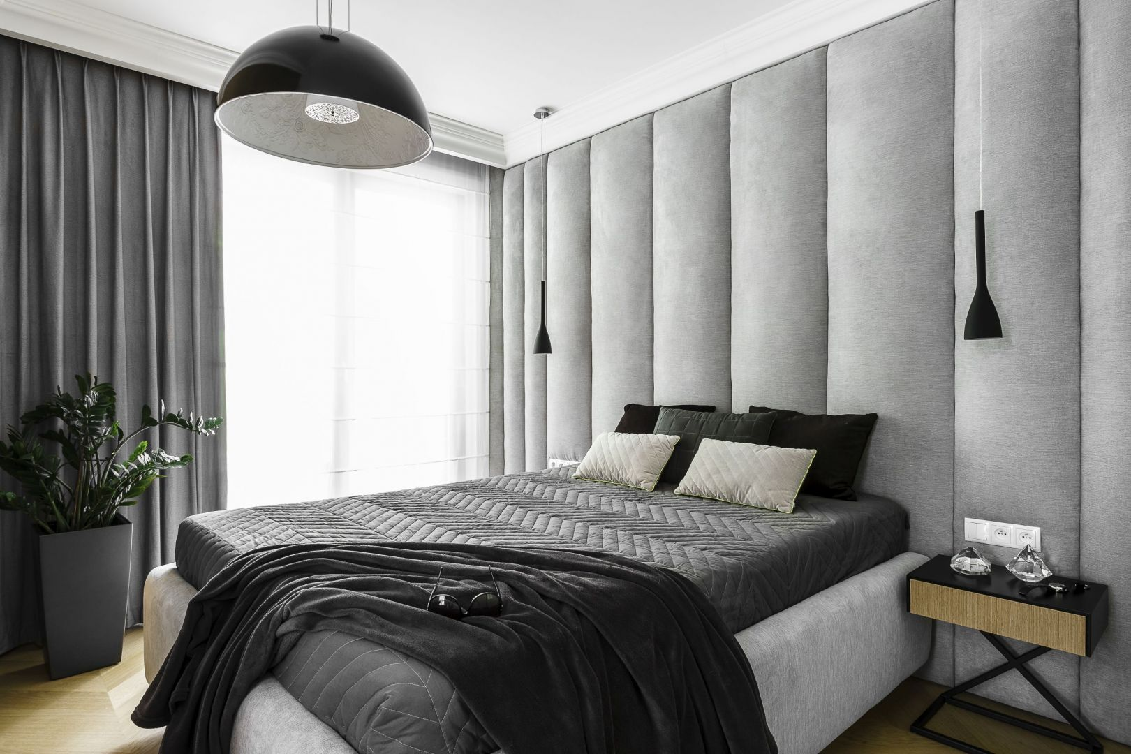 Ściana za łóżkiem w sypialni wykończona jest tapicerowanymi panelami w jasnym szarym kolorze. Panel zdobią całą ścianę za łóżkiem. Projekt: Anna Maria Sokołowska. Fot. Fotomohito