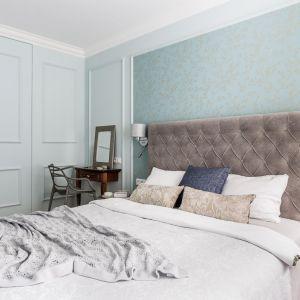 Ściana za łóżkiem w sypialni wykończona jest tapeta w jasnym kolorze. Tapetę zdobi także delikatny wzór. Projekt: Magdalena Bielicka, Maria Zrzelska-Pawlak. Fot. Fotomohito