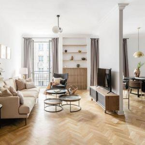Pomysł na mały, ale klasyczny salon w bloku to biel i kolory drewna. Fot. Dziurdzia Projekt