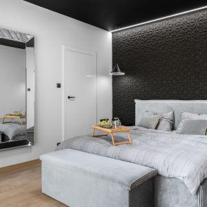Ściana za łóżkiem w sypialni wykończona jest tapetą w czarnym kolorze. Tapeta zdobi całą ścianę. Projekt: Estera i Robert Sosnowscy. Fot. FotoMohito