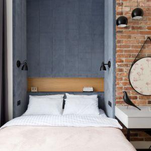 Ściana za łóżkiem w sypialni wykończona jest tapicerowanymi panelami w niebieskim kolorze. Idealnie pasują do cegły na ścianie też obok. Projekt: Anna Maria Sokołowska. Fot. FotoMohito