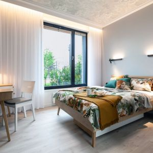 Ściana za łóżkiem w sypialni wykończona jest farbą w szarym kolorze. Projekt: Arkadiusz Grzędzicki Projektowanie Wnętrz. Fot. Olga Kharina, XO foto