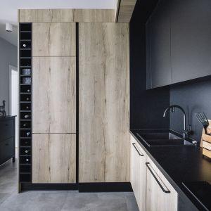 W kuchni czarna kolorystyka frontów łączy się z jasnym i chłodnym drewnem. Projekt: make Architekci. Zdjęcia: Hanna Połczyńska, Kroniki Studio