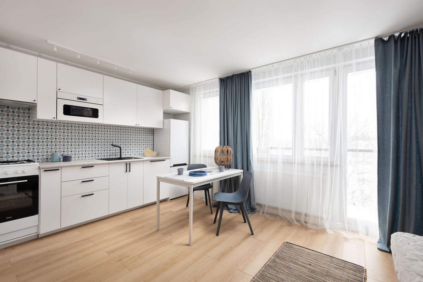 Biała kuchnia, jadalnia, salon i sypialnia to jedna otwarta przestrzeń. Projekt wnętrza, stylizacja: Ola Dąbrówka, pracownia Good Vibes Interiors. Zdjęcia: Mikołaj Dąbrowski