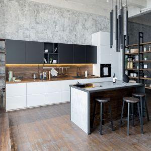 Stylowa kuchnia z wyspą zaaranżowana w jasnych kolorach, z dodatkiem ponadczasowej czerni i naturalnego drewna. Fot. Ferro