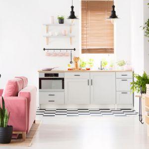 Mała kuchnia w jasnym kolorze, otwarta na salon i z drewnianym blatem. Fot. Ferro