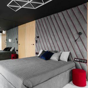 Ściana za łóżkiem w sypialni wykończona jest tapicerowanymi panelami w szarym kolorze. Projekt: Anna Maria Sokołowska. Fot. Fotomohito